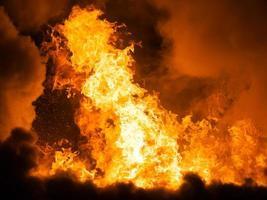 fiamma ardente del fuoco sul tetto della casa in legno foto