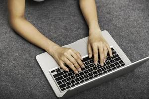 giovane donna posa mentre si utilizza il computer portatile foto