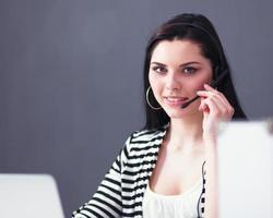 bella donna d'affari, lavorando alla sua scrivania con l'auricolare e foto
