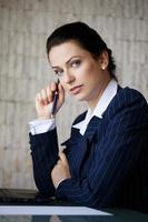 donna di affari che osserva con gli occhi azzurri foto