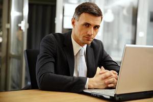 uomo d'affari che si siede con il computer portatile foto