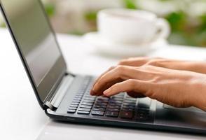 mani della donna che scrivono sul computer portatile foto