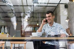 uomo d'affari in un bar parlando al telefono foto