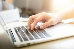 mani della donna che scrivono sulla tastiera del computer portatile: fuoco selettivo foto