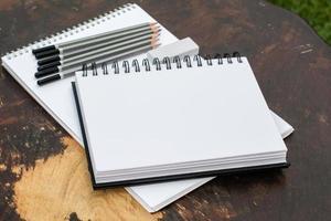 due blocchi da disegno, matite, gomma e il portatile sul tavolo scuro foto