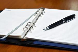 mano con una penna che scrive su carta bianca foto