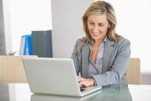 donna di affari che utilizza un computer portatile in un ufficio foto