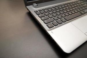 computer portatile d'argento con il primo piano nero della tastiera su uno scrittorio