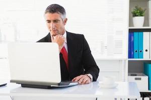 uomo d'affari concentrato in tuta usando il suo computer portatile foto