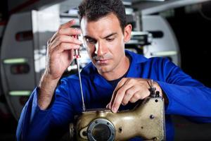 meccanico che ripara macchina per cucire industriale foto
