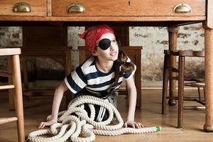 giovane ragazza vestita da pirata, sotto la scrivania
