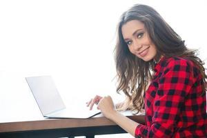 Ritratto di una donna sorridente che per mezzo del computer portatile foto