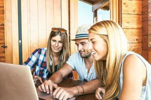 giovane gruppo di amici che utilizzano computer portatile all'aperto foto