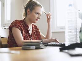 donna che per mezzo del computer portatile al tavolo da pranzo