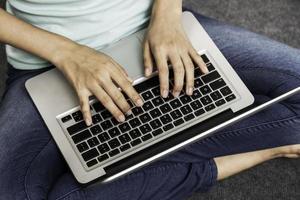 giovane donna seduta mentre si utilizza il computer portatile foto
