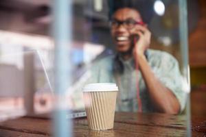 uomo d'affari facendo uso del telefono che lavora al computer portatile nella caffetteria foto