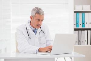 medico serio che per mezzo del computer portatile foto