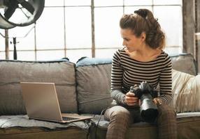 giovane donna con la macchina fotografica moderna del dslr che per mezzo del computer portatile foto