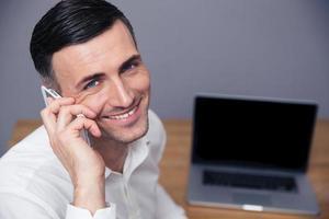 uomo d'affari sorridente che parla al telefono foto