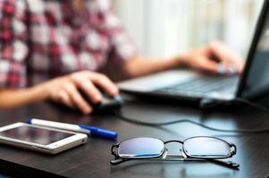 occhiali sul tavolo di fronte a lavorare allo studente di computer foto