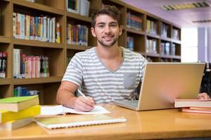 studente che studia nella biblioteca con il computer portatile
