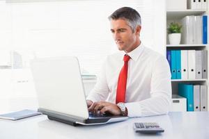 uomo d'affari allegro che scrive sul computer portatile foto