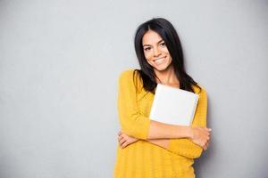 donna sorridente che sta con il computer portatile foto