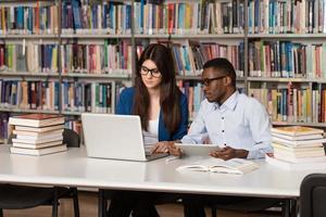 coppia di studenti con il portatile in biblioteca foto