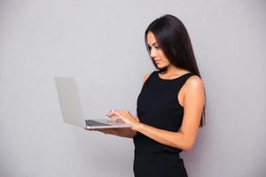 Ritratto di una bella donna d'affari utilizzando il computer portatile foto