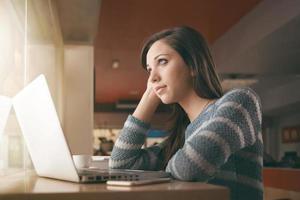 ragazza dell'adolescente che per mezzo di un computer portatile foto