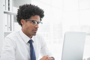 uomo d'affari concentrato che guarda il suo computer portatile foto