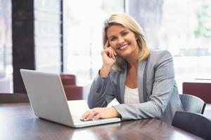 donna di affari bionda che sorride per mezzo del computer portatile foto