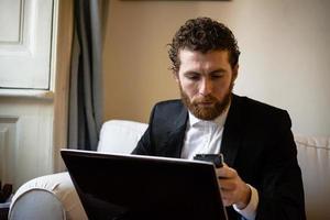 uomo elegante dei pantaloni a vita bassa bei che per mezzo del computer portatile foto