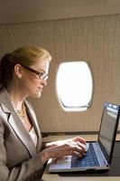 donna di affari che per mezzo del computer portatile sull'aeroplano, vista laterale foto