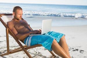 uomo che per mezzo di un computer portatile mentre si rilassa sulla sua sedia a sdraio foto