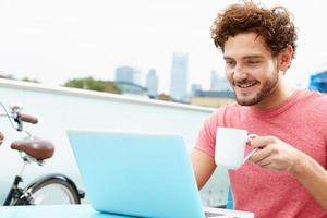 giovane uomo seduto sulla terrazza sul tetto con laptop foto