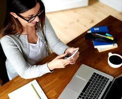 donna seduta alla scrivania guardando il telefono cellulare foto