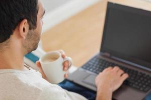 uomo bello che beve caffè mentre si utilizza il suo computer portatile
