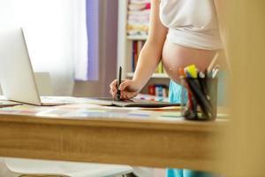 donna incinta che lavora da casa foto