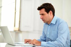 uomo d'affari bello 30s che lavora con il suo computer portatile foto