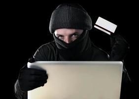 uomo del pirata informatico nel nero facendo uso del concetto del crimine informatico del computer portatile foto