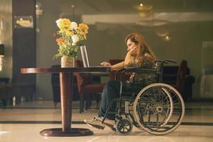 sedia a rotelle guardare il computer foto