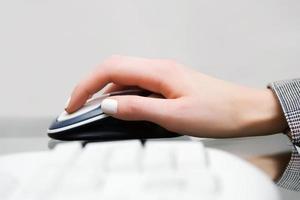 mano femminile che tiene il mouse del computer foto