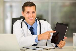 giovane medico che punta computer tablet foto