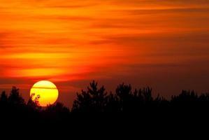 sole che tramonta in un fumoso cielo occidentale foto