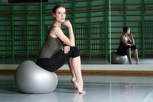 donna che si siede con la palla di esercizio foto
