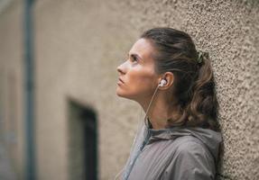 Ritratto di musica d'ascolto della giovane donna di forma fisica all'aperto foto