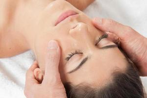 la donna si fa un massaggio in faccia foto