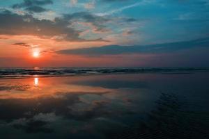 alba maligna al tramonto cielo rosso in mare. foto