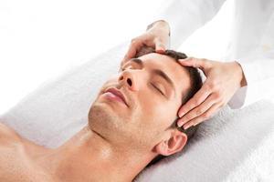 primo piano di un uomo che ha massaggio alla testa foto